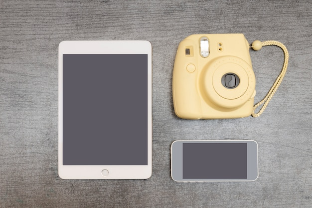 Gelbe kamera, eine tablette und ein smartphone auf einer schwarzen tabelle. ansicht von oben