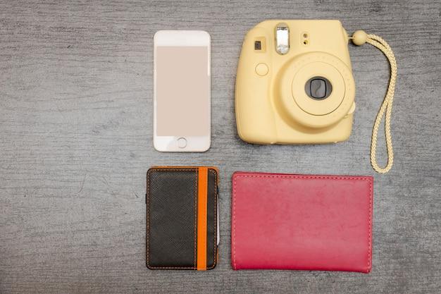 Gelbe kamera, smartphone, geldbörse und reisepass