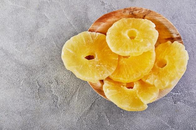 Gelbe kandierte ananasringe auf einer grauen betonoberfläche in einer holzplatte