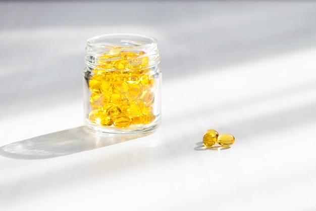 Gelbe kapseln mit vitamin d, fischöl omega 3 mit sonnenlicht auf weißem holzhintergrund. gesundes und medizinisches konzept.