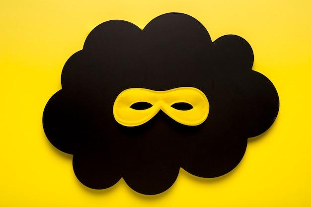 Gelbe karnevalsmaske der draufsicht auf schwarzer papierwolke