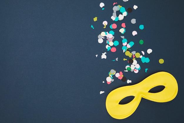 Gelbe karnevalsmaske und mehrfarbige konfetti über farbigem hintergrund