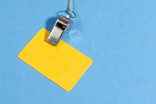 Gelbe karte und schiedsrichterpfeife mit platz für text auf blauem hintergrund