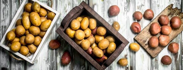 Gelbe kartoffeln in der schachtel und auf dem tablett und rote kartoffeln auf dem schneidebrett. auf hölzernem hintergrund