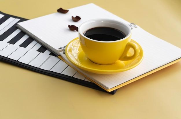 Gelbe keramiktasse mit schwarzem kaffee auf geöffnetem buch und klaviertasten, verschwommenes licht herum