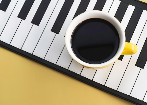 Gelbe keramiktasse mit schwarzem kaffee auf klaviertasten, pastellfarbener hintergrund