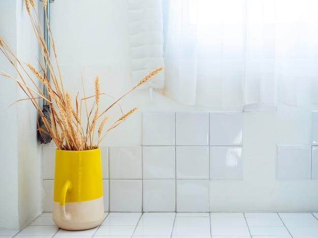 Gelbe keramikvase mit getrockneten reispflanzen auf weißer, sauberer gitterfliesenwand in der nähe des fensters mit weißem transparentem stoffvorhang mit kopierraum.