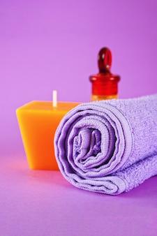 Gelbe kerze und aromaöl, violettes handtuch