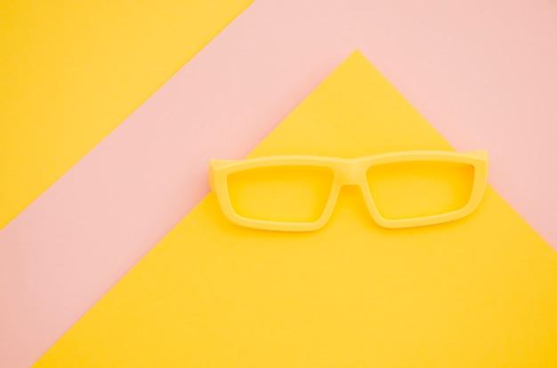 Gelbe kinderbrillen auf rosa und gelbem hintergrund