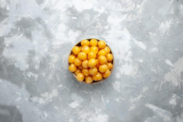 Gelbe kirschen der draufsicht innerhalb der platte auf dem frischen sommerfarbfoto der graulichtschreibtischfruchtfrucht