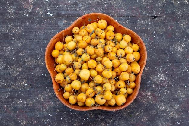 Gelbe kirschen der draufsicht süße milde und saftige innenplatte auf dem frischen süßkirschfoto der grauen hintergrundfruchtfrucht