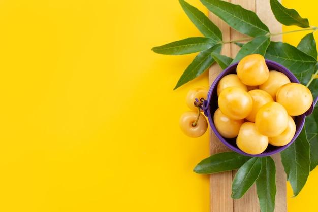 Gelbe kirschen der draufsicht weich und süß mit grünen blättern auf gelbem schreibtisch, fruchtfarbene sommer-süßkirsche