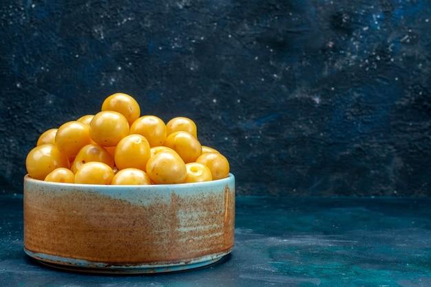 Gelbe kirschen in brauner runder schüssel auf dunkel