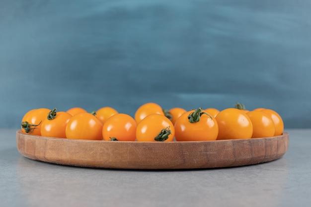 Gelbe kirschtomaten lokalisiert auf einem konkreten grauen tisch.