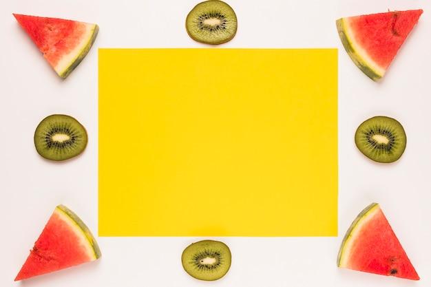 Gelbe klebrige anmerkung geschnittene rote wassermelone und kiwi