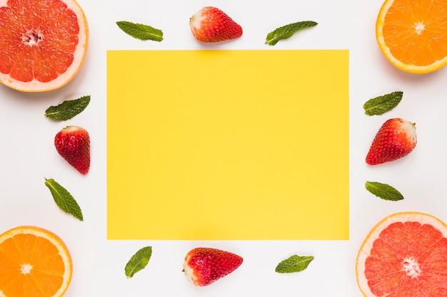 Gelbe klebrige anmerkung schnitt orange erdbeer- und grünblätter der saftigen pampelmuse