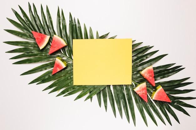 Gelbe klebrige anmerkung und geschnittene rote wassermelone am palmblatt