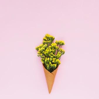 Gelbe kleine blumen innerhalb des waffelkegels gegen rosa hintergrund