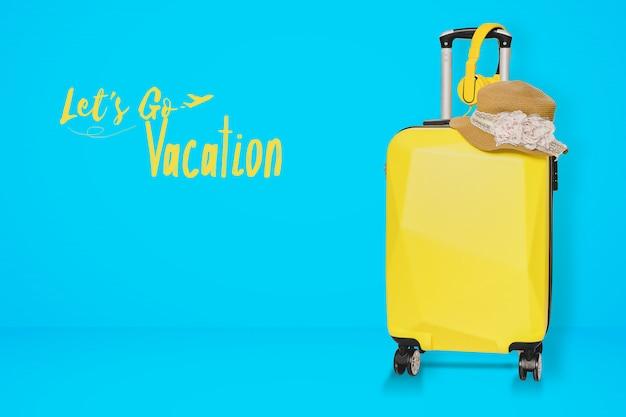 Gelbe koffertasche mit hut und kopfhörer auf blauem hintergrund.