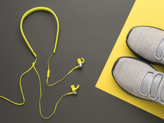 Gelbe kopfhörer mit einem draht und grauen turnschuhen auf einem grauen und gelben hintergrund. sportlicher lebensstil. farben 2021.