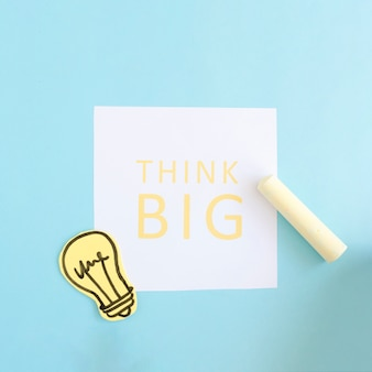 Gelbe kreide und papierausschnittglühlampe an denken großen text über weißbuch auf blauem hintergrund