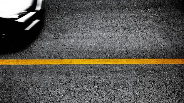 Gelbe lacklinie auf schwarzem asphalt