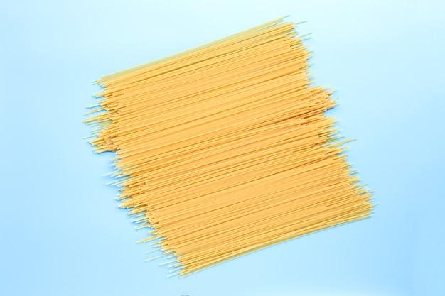 Gelbe lange spaghetti auf blauer oberfläche