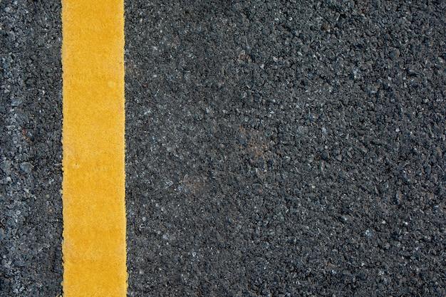 Gelbe linie auf schwarzem asphaltstraßenhintergrund mit kopienraum