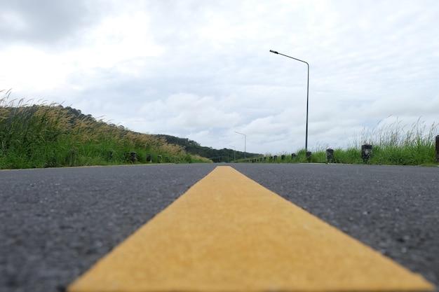 Gelbe linie mit asphaltstraßenbeschaffenheit vor xamountain view close up