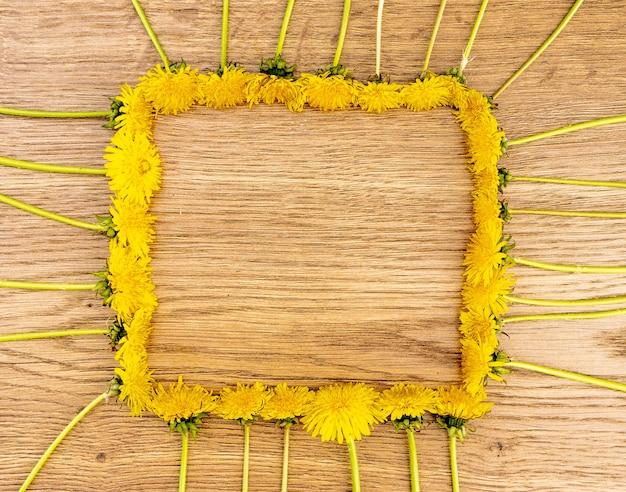 Gelbe löwenzahnblumen auf einem hölzernen hintergrund. draufsicht, die blumen sind in form eines quadratischen rahmens angeordnet