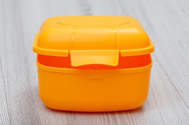 Gelbe lunchbox aus kunststoff auf der grauen holzoberfläche