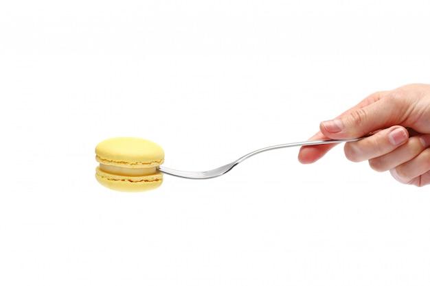 Gelbe makronen auf einer gabel. süße und französische makronen auf weißer wand. makronen in der hand.