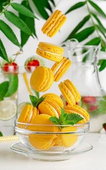Gelbe makronen fallen in die glasschale. französisches dessertkonzept
