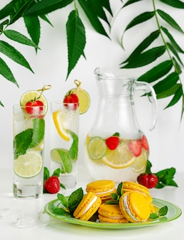 Gelbe makronen und limonade mit limette, minze und erdbeeren auf weißem raum. vertikale