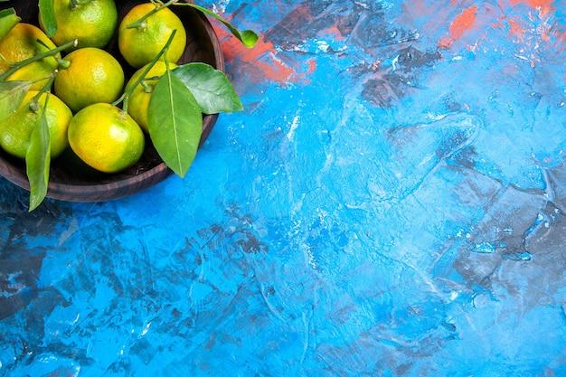 Gelbe mandarinen der draufsicht mit blättern in der holzschale auf blauer oberfläche mit kopienraum