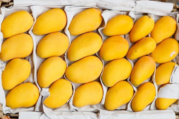 Gelbe mango, die im kasten auf obstmarkt liegt