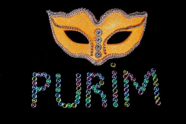 Gelbe maske mit text purim auf schwarzem hintergrund. jüdischer feiertag.