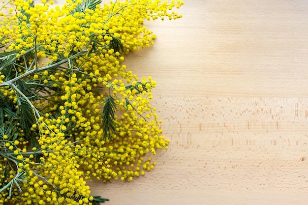 Gelbe mimosenblumen auf dem naturholzhintergrund
