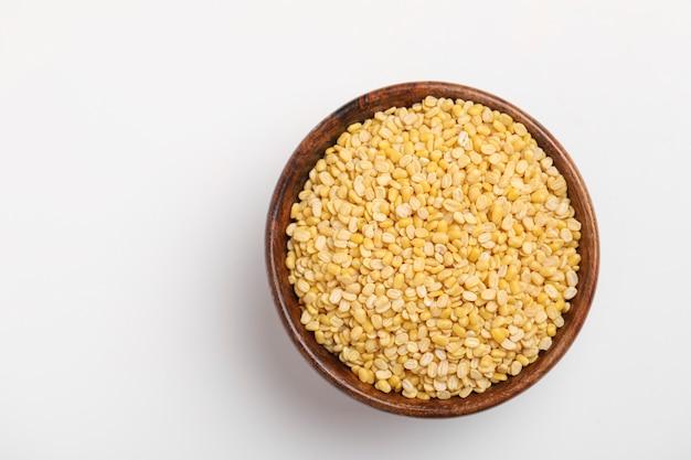 Gelbe moong mung dal linsenpulsbohne in der holzschale auf weißem hintergrund
