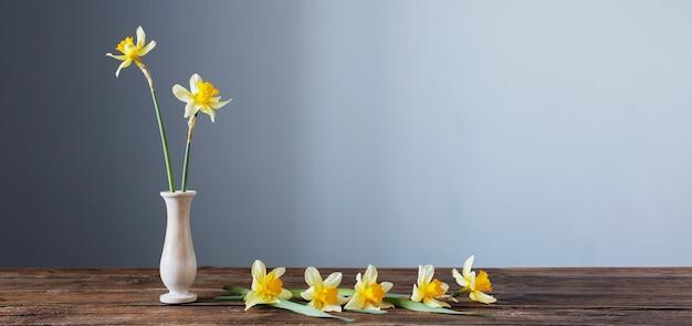 Gelbe narzisse in vase auf holztisch auf dunklem hintergrund