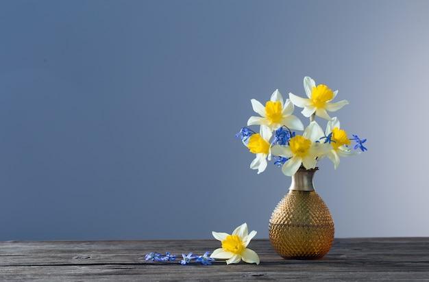 Gelbe narzisse und blaue schneeglöckchen in der vase auf holztisch auf dunkler oberfläche