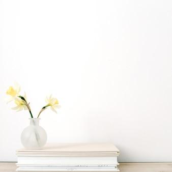 Gelbe narzissenblume im blumentopf auf fotoalben vor weißem hintergrund.