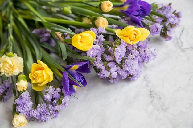 Gelbe narzissenblumen und lila iris in einer linie blumenanordnung lokalisiert auf marmorhintergrund.