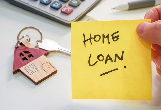Gelbe note mit formulierung home loan mit hausschlüsselanhänger und taschenrechner