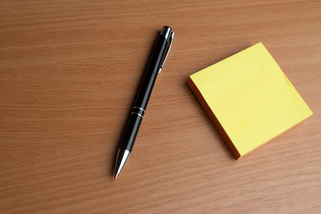 Gelbe notizblöcke mit schwarzem stift auf dem hölzernen schreibtisch