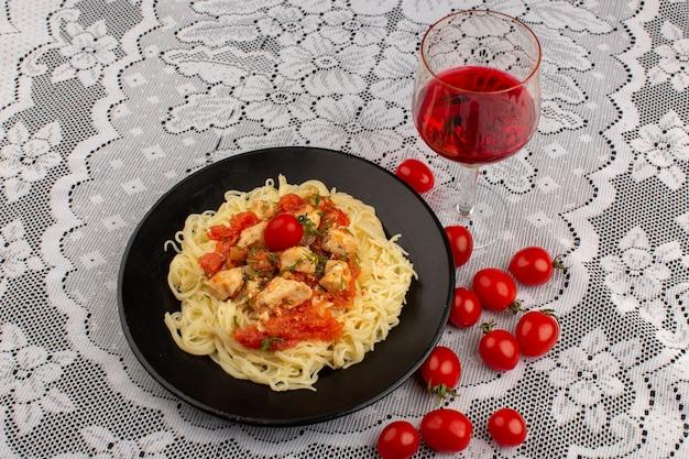 Gelbe nudeln der draufsicht, gekocht mit hühnerflügeln und tomatensauce innerhalb der schwarzen platte auf dem weißen gedeckten tisch