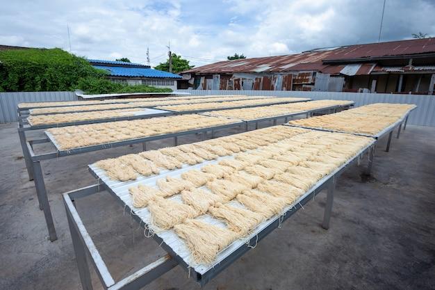Gelbe nudeln oder lebensmitteltrockner mee sua im sonnenlicht, das die sonne in thailand getrocknet macht
