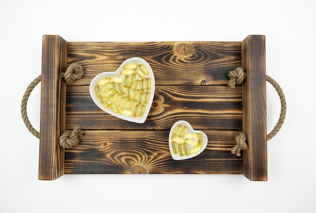 Gelbe omega-3-kapseln liegen auf weißen keramikplatten in form der herzen auf einem holztablett