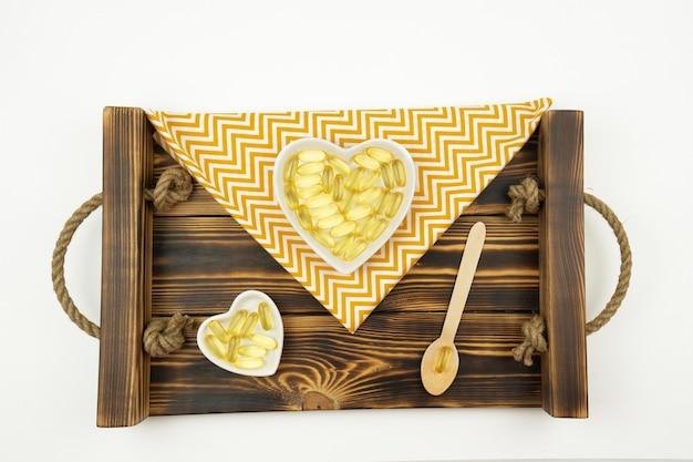 Gelbe omega-3-kapseln liegen in form der herzen auf weißen keramikplatten