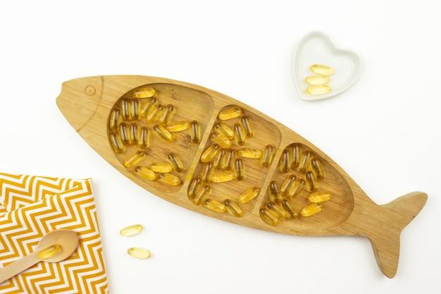 Gelbe omega-3-kapseln liegen in form des fisches auf einem holzteller